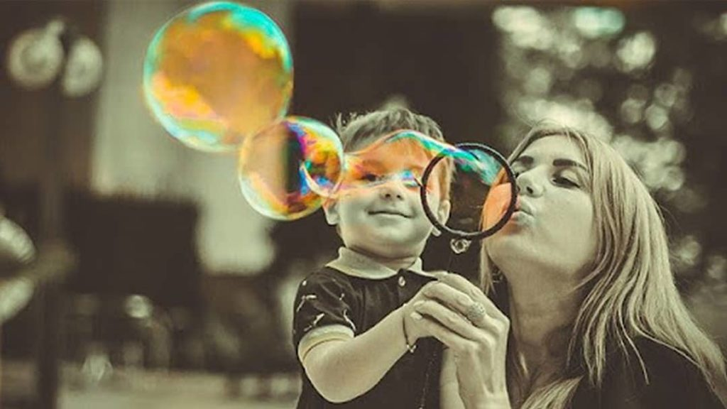 Mom Blowing Bubbles With Son